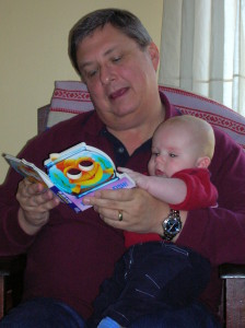 man reading book to baby